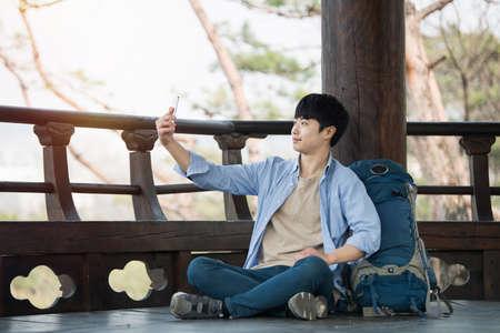 Ein junger Mann , der reist , um Korea , die Bilder mit seinem Smartphone zu machen Standard-Bild - 98887425