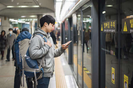 Young man traveling to Korea, male waiting for subway Standard-Bild - 99166472