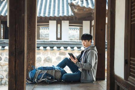 Junger Mann , der in Korea arbeitet . Sitzen in einem traditionellen traditionellen Haus und mit einem Tablet-Computer Standard-Bild - 99520679