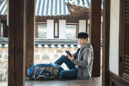 Young man traveling in Korea. sitting in a Korean traditional house and using a tablet computer. Zdjęcie Seryjne