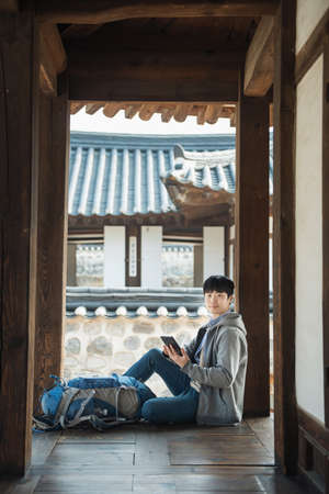 Young man traveling in Korea. sitting in a Korean traditional house and using a tablet computer. Stok Fotoğraf