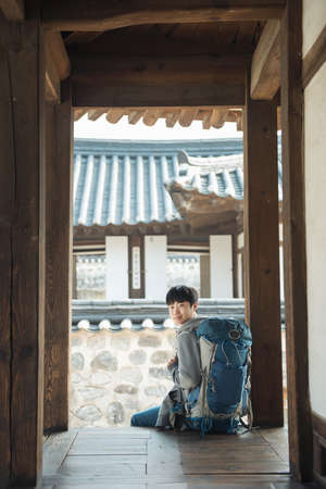 Young man traveling in Korea. Korean traditional house