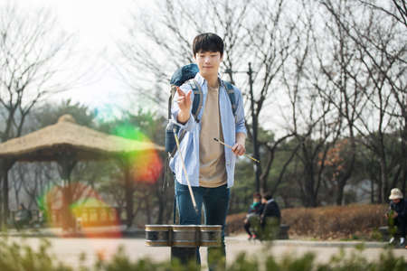 Young man traveling in Korea. Korean traditional play