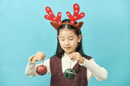 Asian girl with a Christmas concept headdress Child, Close up of cute little asian girl on blue background isolated. Stock Photo