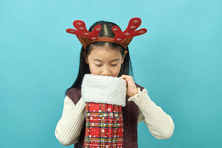 Asian girl with a Christmas concept headdress Child, Close up of cute little asian girl on blue background isolated. Zdjęcie Seryjne