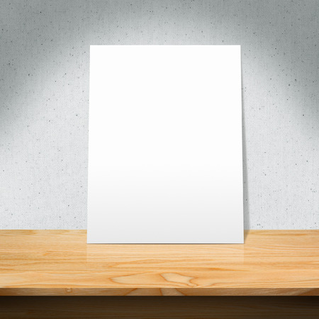 White poster on a wooden table with concrete wall background 版權商用圖片 - 39761731