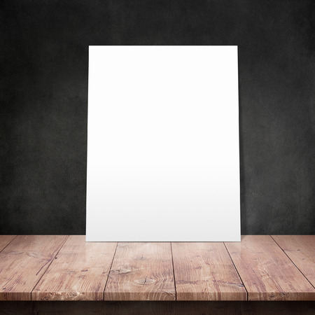 kitchen floor: White poster on a wooden table with concrete wall background