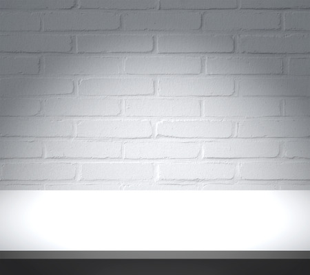 White table with brick wall background Standard-Bild
