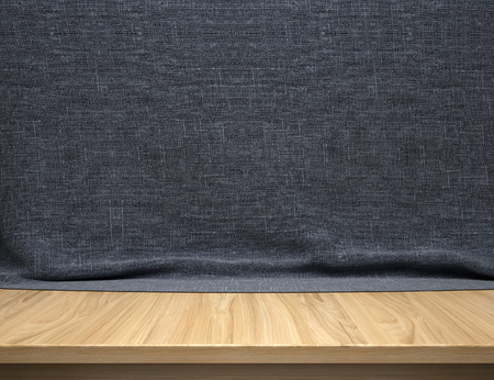Wood table with dark blue cotton fabric background