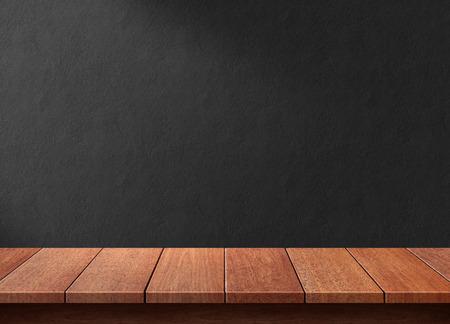 黒い壁の背景の木のテーブル