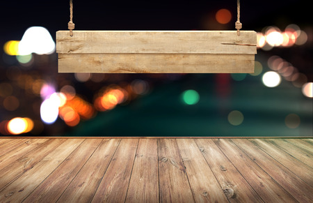 Wood table with hanging wooden sign on city lights night blurred background