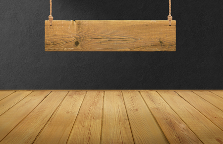 Wood table with hanging wooden sign on black concrete wall Standard-Bild