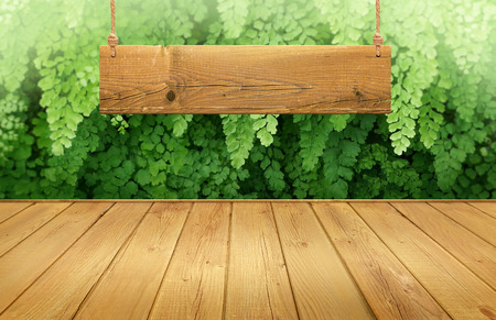 Wood table with hanging wooden sign on green leaves background
