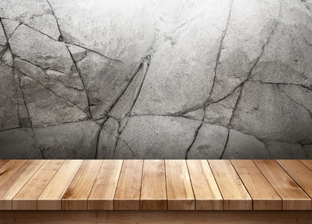 Wood table with cracked stone wall background