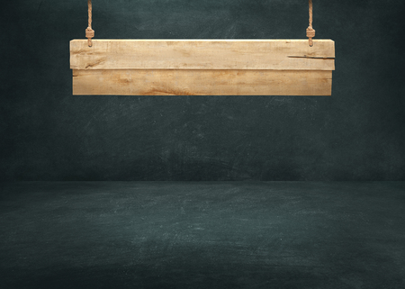 Wooden signboard hanging on dark background wall