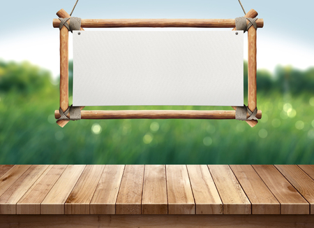 Wood table with hanging wooden sign on green nature blurred background Standard-Bild