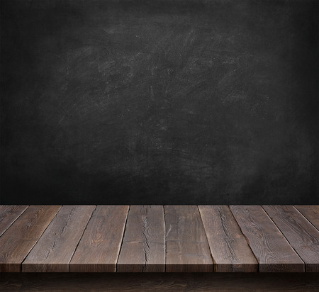 Mesa de madera con el fondo de pizarra Foto de archivo