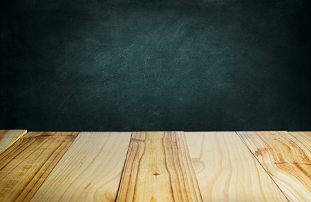 Wood table and blackboard background Фото со стока