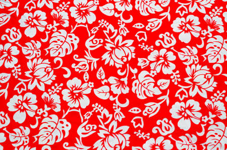 ferns and orchids: Red Hawaiian fabric with white flowers Stock Photo