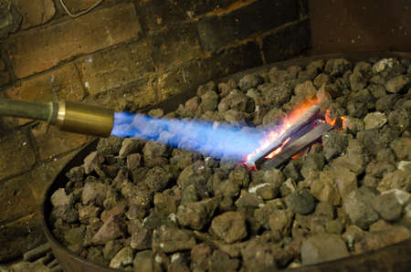blowtorch: Black smith heating steel knife with blowtorch Stock Photo