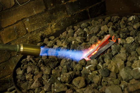 blowtorch: Black smith heating hot steel knife with blowtorch
