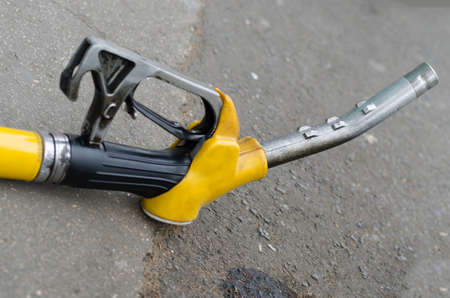 gas nozzle: Yellow gas nozzle on the sidewalk