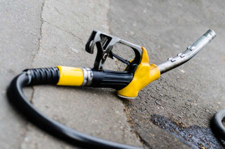 unleaded: Yellow gas nozzle isolated on the sidewalk