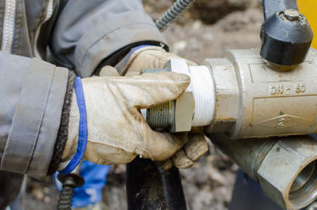 pipe connector: Man working on pipe connector with tape and gloves Stock Photo