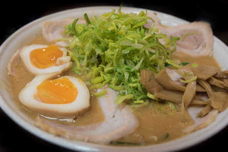 porc: Closeup of a ramen  noodle soup with porc, chives, eggs, bamboo and leek isolated on black background