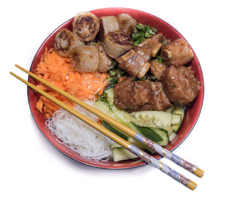 porc: Bowl of beef Bo bun with salad, porc ribs, fresh herbs and chinese chopsticks