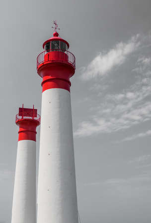 grey sky: Two white and red lighthouses isolated on grey sky with clouds Stock Photo