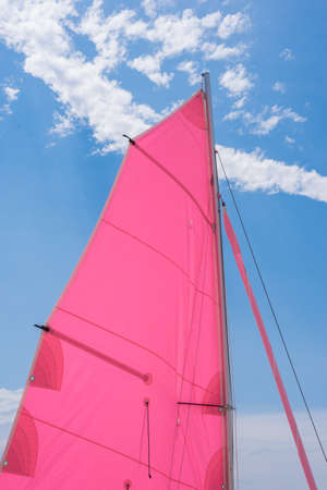 sailboard: Pink colorful  sails of a sailboat on a beautiful blue cloudy sky Stock Photo