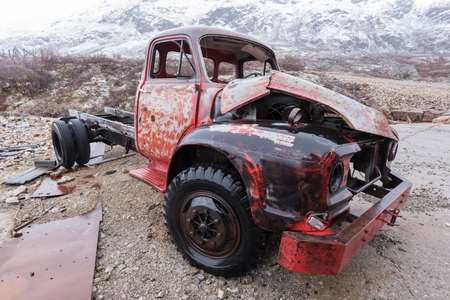 oldie: Abandoned old red pick up truck  decaying in a snowy moutain  landscape Stock Photo