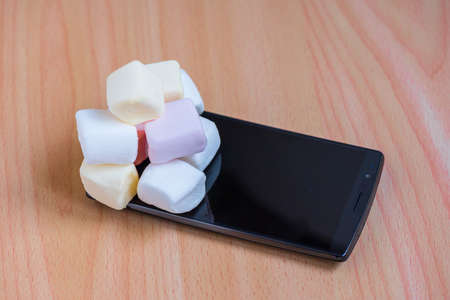 os: Yellow, pink and white marshmallow on a smart phone