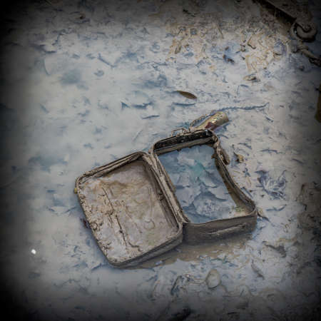 emptying: Old suitcase burried in the sludge and full of leaves during the emptying of the canal St-Martin