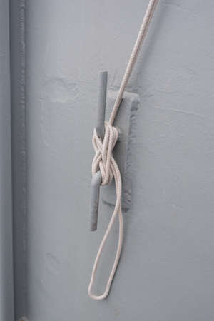 mooring bollards: Metallic cleat with a white rope on a grey wall