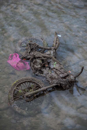 emptying: Old motorcycle burried in the sludge with pink plastic bag during the emptying of the canal St-Martin