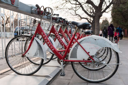 Beijing,  China December 13th 2016: Public bikes renting station with red and white bikes ready to be rented Editorial
