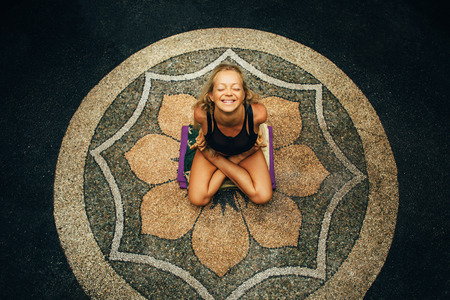 Blondynka z opaloną smukłym ciele sprawia, że ćwiczenia jogi na zewnątrz w środku kwiatowym i śmiechem. Yoga