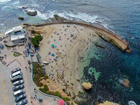 Beachgoers enjoying a beautiful sunny afternoon at La Jolla Cove in San Diego, CA. USA.