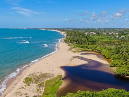 Aerial view of river merging to tropical white sand beach and turquoise clear sea water. Praia do Forte, Bahia, Brazil. Travel tropical destination Stock Photo