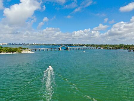 Aerial view of open street bridge crossing ocean with small boat and linking Island Bay and Sarasota, Florida, USA