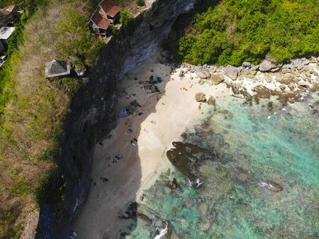 Aerial view of an amazing little beach with rock cliff in Bali. Beautiful sea water with waves for surfing. Ocean landscape, holiday destination