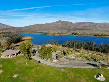 Aerial view of little park in front of Otay Lake City Reservoir with blue sky and mountain on the background, Chula Vista, California. USA 写真素材