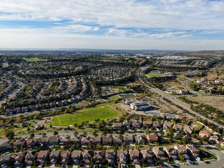 Aerial view of upper middle class neighborhood with identical residential subdivision houses during sunny day in Chula Vista, California, USA.