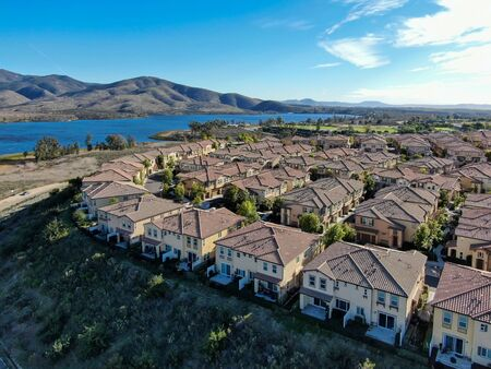 Aerial view of identical residential subdivision condo with big lake and mountain on the background during sunny day in Chula Vista, California, USA.