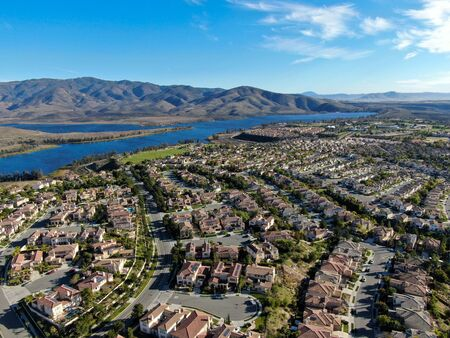 Aerial view of identical residential subdivision house with big lake and mountain on the background during sunny day in Chula Vista, California, USA. 免版税图像 - 136490378