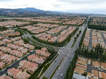 Aerial view of urban sprawl. Suburban packed homes neighborhood with road.during clouded day. Vast subdivision in Irvine, California, USA Фото со стока
