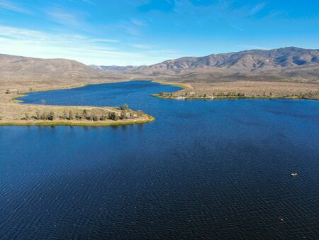 Aerial view of Otay Lake Reservoir with blue sky and mountain on the background, Chula Vista, California. USA