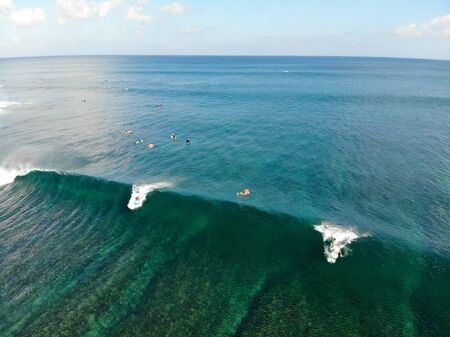 Aerial view of surfers on their board catching the waves,, big waves tropical blue ocean, Bali, Indonesia